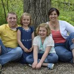 Family of 4 sitting beneath a tree